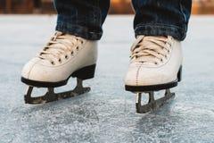 Una chica joven que se coloca en patines en una charca congelada en el hielo Fotografía de archivo