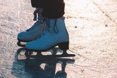 Una chica joven que se coloca en patines en una charca congelada en el hielo Luz suave agradable de la puesta del sol Fotografía de archivo