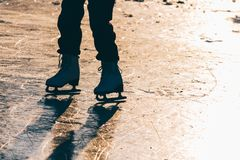 Una chica joven que se coloca en patines en una charca congelada en el ic Fotos de archivo libres de regalías