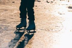 Una chica joven que se coloca en patines en una charca congelada en el ic Imágenes de archivo libres de regalías