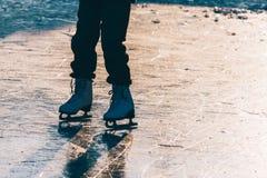 Una chica joven que se coloca en patines en una charca congelada en el ic Fotografía de archivo libre de regalías