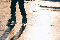Una chica joven que se coloca en patines en una charca congelada en el ic Imagen de archivo libre de regalías