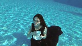 Una chica joven que se sienta bajo el agua en la parte inferior de la piscina en un vestido de Borgoña, bebiendo de una taza blan almacen de video