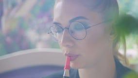 Una chica joven que se sienta en un café que fuma una cachimba, exhalando lentamente humo blanco grueso metrajes