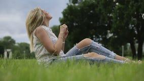 Una chica joven que se sienta en una hierba almacen de video