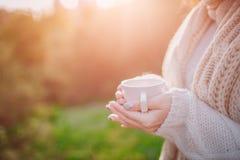 Una chica joven que sostiene una taza de bebida caliente y que sonríe en el fondo de una mujer joven atractiva del bosque del oto imágenes de archivo libres de regalías