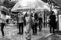 Una chica joven que sostiene un paraguas en la lluvia fotos de archivo