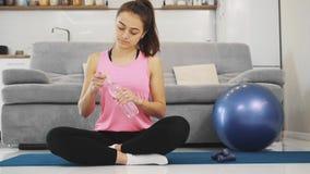 Una chica joven que termina haciendo ejercicio físico se adhiere a las reglas del régimen del agua