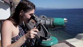 Una chica joven se coloca en la plataforma de observación que pasa por alto el mar y mira a través de un telescopio almacen de metraje de vídeo