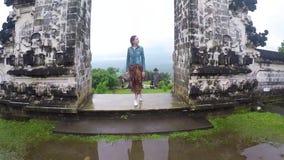 Una chica joven se coloca en la puerta del templo Lempuyang La cámara se levanta y tiró la reflexión en el agua almacen de video