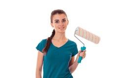 Una chica joven se coloca sonriente y que sostiene un rodillo para pintar aislado en el fondo blanco fotografía de archivo