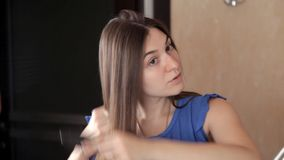 Una chica joven se está colocando delante de un espejo y se está peinando el pelo largo metrajes