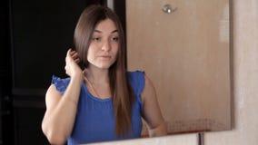 Una chica joven se está colocando delante de un espejo y se está peinando el pelo largo almacen de metraje de vídeo