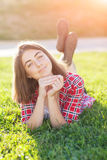 Una chica joven se está sentando al aire libre en la hierba en un árbol, mirada del empollamiento, un día de verano al aire libre Fotografía de archivo