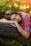 Una chica joven se está sentando al aire libre en la hierba en un árbol, mirada del empollamiento, un día de verano al aire libre Foto de archivo