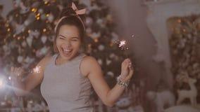 Una chica joven se está sentando cerca del árbol del Año Nuevo en el cuarto con la decoración y las luces de la Navidad almacen de video