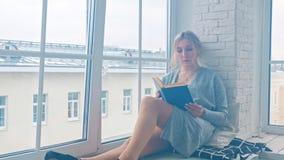 Una chica joven se está sentando en el alféizar y está leyendo un libro almacen de metraje de vídeo