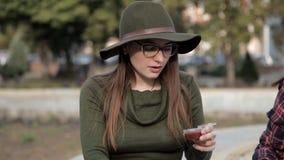 Una chica joven se está sentando en el parque y está intentando una salsa deliciosa El caminar, comiendo almacen de video