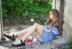 Una chica joven se está sentando en la abertura de la ventana, en el edificio devastado en el parque, Foto de archivo