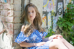 Una chica joven se está sentando en la abertura de la ventana, en el edificio devastado en el parque, Imágenes de archivo libres de regalías