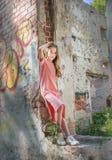 Una chica joven se está sentando en la abertura de la ventana, en el edificio devastado en el parque, Fotos de archivo libres de regalías