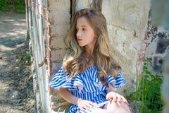 Una chica joven se está sentando en la abertura de la ventana, en el edificio devastado en el parque, Imagenes de archivo