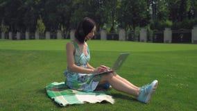Una chica joven se sienta en la manta y mecanografiar en un ordenador portátil al aire libre almacen de video