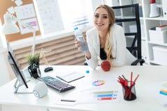 Una chica joven se sienta en una tabla en la oficina y sostiene una botella de agua en su mano Antes de la muchacha en la tabla e imagen de archivo