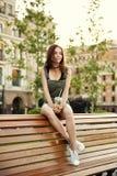 Una chica joven se sienta en un banco en la ciudad, con una bebida en su ha Imagenes de archivo