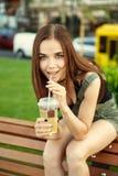 Una chica joven se sienta en un banco en la ciudad, con una bebida en su ha Fotos de archivo libres de regalías
