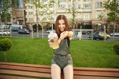 Una chica joven se sienta en un banco en la ciudad, con una bebida en su ha Imagen de archivo
