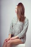 Una chica joven se sienta en un cubo Ella puso sus manos en sus rodillas desnudas En un suéter gris Photoshoot en estudio de la f Imagenes de archivo