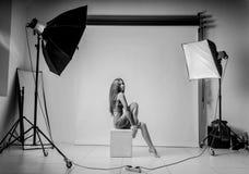 Una chica joven se sienta en un cubo Ella puso sus manos en sus rodillas desnudas En un suéter gris Photoshoot en estudio de la f Fotografía de archivo
