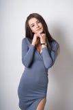 Una chica joven se sienta en un cubo Ella puso sus manos en sus rodillas desnudas En un suéter gris Photoshoot en estudio de la f Fotos de archivo libres de regalías