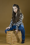 Una chica joven se sienta a horcajadas en una maleta de mimbre Fotos de archivo libres de regalías