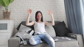 Una chica joven sonriente alegre se sienta en el sof? y lanza para arriba d?lares _concepto bueno suerte y beneficio, motivaci?n