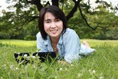 Una chica joven sonriente con la computadora portátil al aire libre Imagenes de archivo