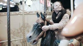 Una chica joven sube un caballo del juguete en un parque de atracciones Los paseos alegres de la muchacha en un feliz van ronda q almacen de video