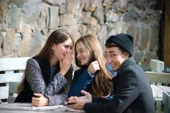 Una chica joven susurra algo a su oído del ` s del amigo Imagen de archivo