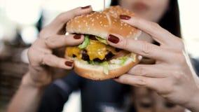Una chica joven tiene un cheeseburger apetitoso grande Lo sostiene en las manos almacen de video