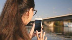 Una chica joven toma imágenes en el teléfono Puente hermoso en el río El paisaje pintoresco Primer Día asoleado metrajes