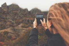 Una chica joven toma las fotos de un paisaje de la montaña del otoño Día brumoso foto de archivo