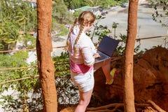 Una chica joven trabaja con un ordenador portátil en la montaña que pasa por alto la selva tropical y la playa Trabajo y viaje foto de archivo libre de regalías
