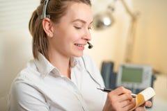 Una chica joven trabaja en un centro de atención telefónica Para un lugar de trabajo datos de la grabaci?n En el auricular con un fotos de archivo