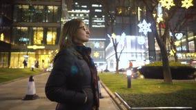 Una chica joven vestida en una chaqueta negra y los vidrios, lentamente paseos en el medio de la ciudad entre las tiendas y metrajes
