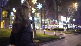 Una chica joven vestida en una chaqueta negra y los vidrios, lentamente paseos en el medio de la ciudad entre las tiendas y almacen de metraje de vídeo