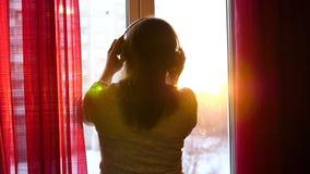 Una chica joven viene a la ventana y viste los auriculares para escuchar la música Fondo borroso con puesta del sol, mujer almacen de video