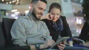 Una chica joven y su novio están jugando a un juego en la tableta y la risa metrajes