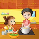 Una chica joven y un muchacho en la cocina Imágenes de archivo libres de regalías