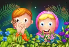 Una chica joven y un muchacho que ocultan en el jardín Imagen de archivo libre de regalías